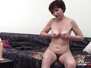 Adult with saggy tits moans in pleasure while using a toy on her snatch.
